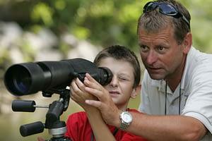 man teaching a boy to use a scope