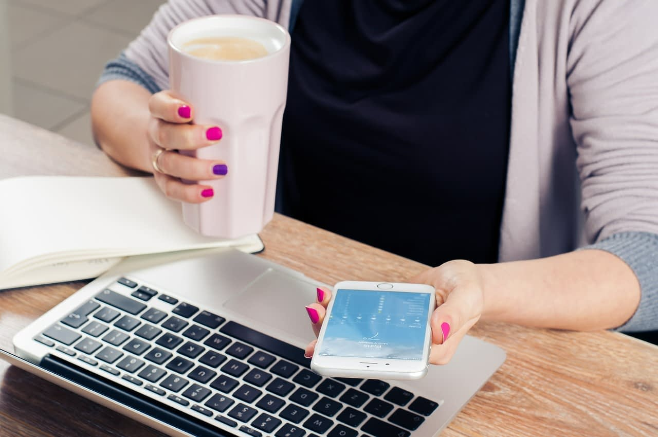 using an iPhone and laptop while having a coffee